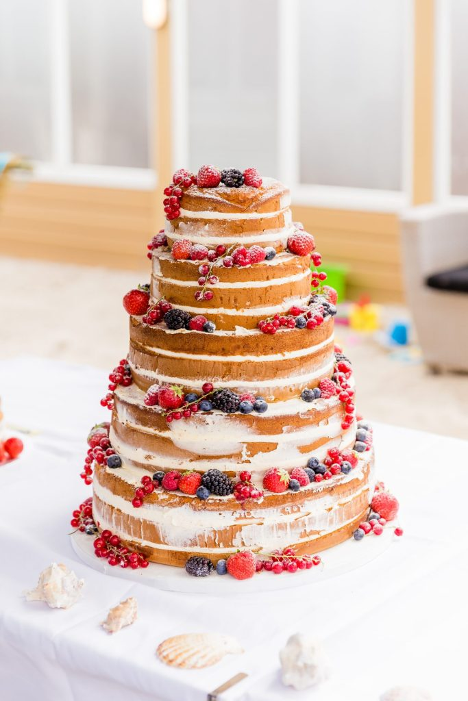 Een prachtige naakte bruidstaart gedecoreerd met vers rood fruit.