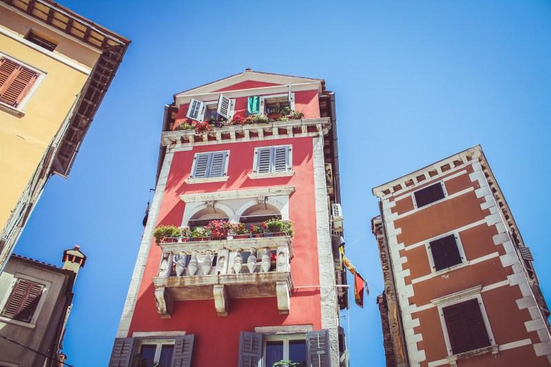 Rotes Haus vor blauem Himmel mit Blümchen am Balkon