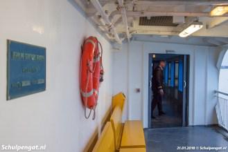 Aangezien de Schulpengat voor de laatste keer in de vaart is, neemt de kapitein van het schip tijdens de overtocht een kijkje aan dek. Links hangt de werfplaat uit Heusden.