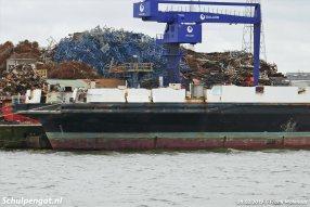 De hopen met schroot stapelen zich op naast de voormalige TESO-veerboot Schulpengat in Gent.