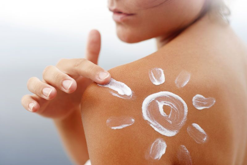 woman putting sunscreen on her shoulder