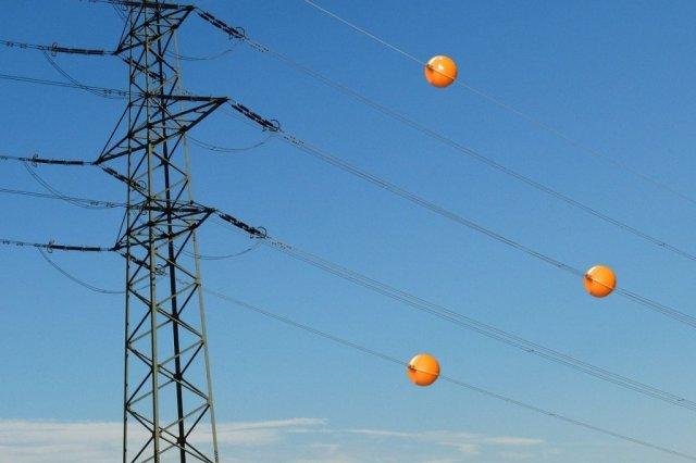 Pra que servem as bolas de plástico coloridas que ficam penduradas nos fios de energia?