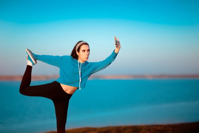 Girl in Yoga Pose Taking a Selfie Outside in Nature( Nicoleta Ionescu)s