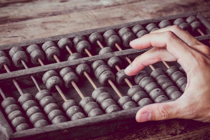 Tom vintage das mãos do homem, contabilidade com o velho ábaco e segure a calculadora eletrônica (Patty Chan) s