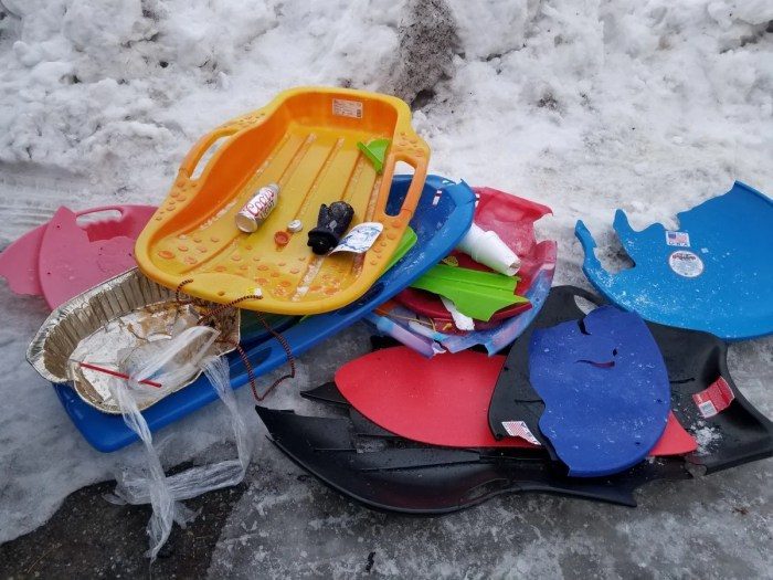 broken sleds and discarded beer cans line the snow covered ground