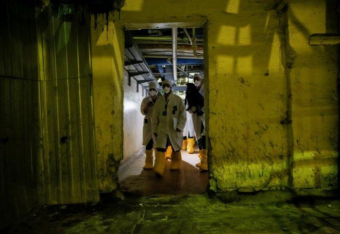 Journalists walk through the corridor of one of Chernobyl's reactors. (Gleb Garanich/Reuters)