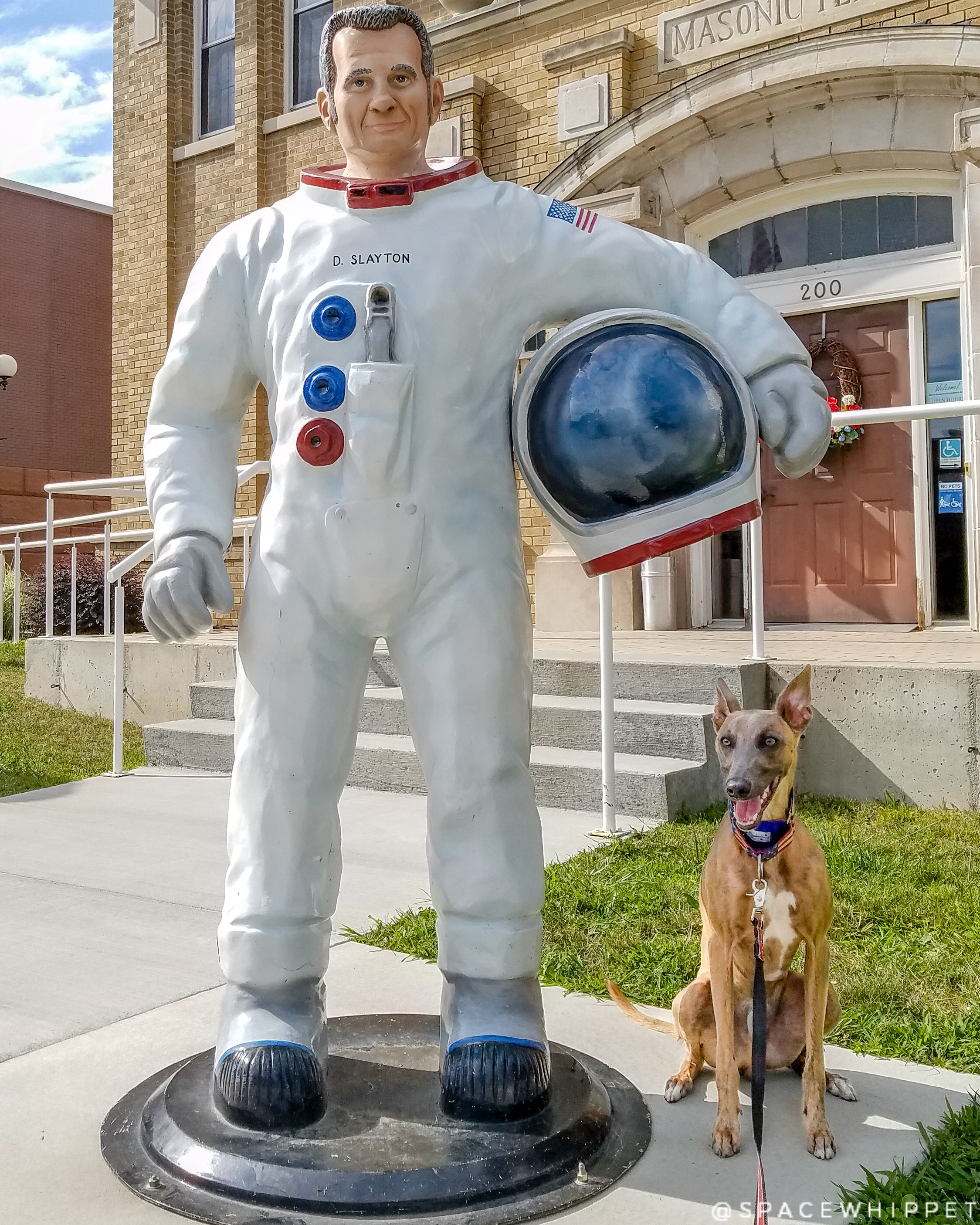 Kuiper poses with a statue of Deke Slayton in a spacesuit.