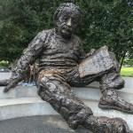Kuiper stands under the arm of a large statue of Albert Einstein.