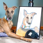 Kuiper poses with a drawing of himself. They are wearing the same collar and their ears are in the same position.