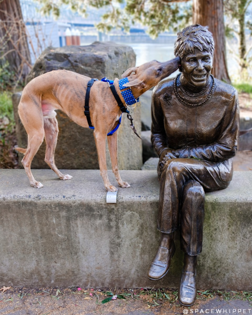 Kuiper whispers a secret into the ear of a seated statue of Vera Katz.
