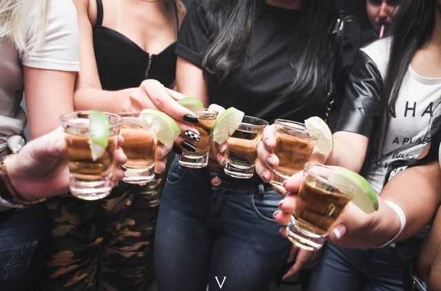 women holding shot glasses drinking