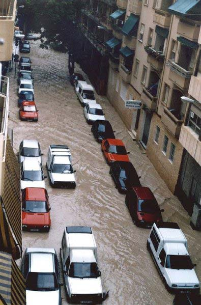 Looking down a flooded street from the view of an apartment window, this photo shows a large number of flooded cars that have been drenched in the heavy rainfall.