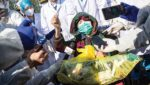 person in mask surrounded by doctors and reporters