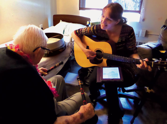 music therapist playing guitar with an old man holding drum sticks
