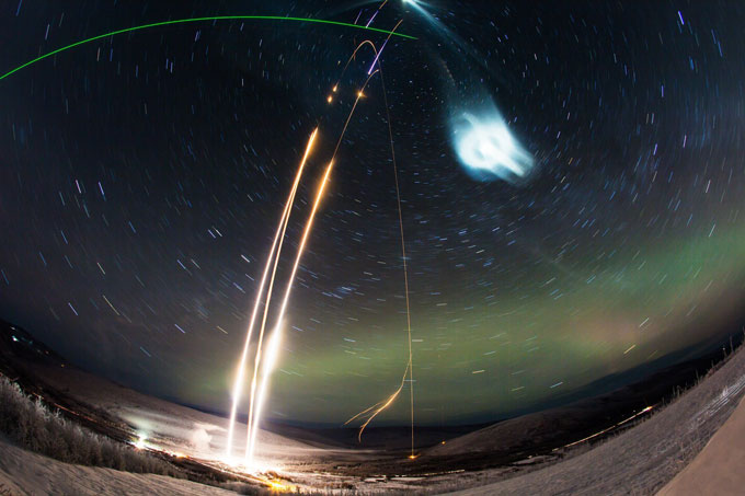 time-lapse photo of three rocket launches and chemical tracers in night sky
