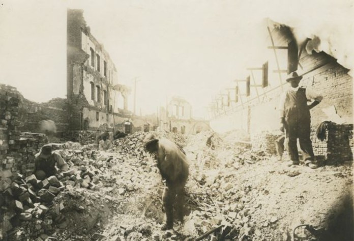 Three men salvage bricks from the ruins of the Gurley Hotel