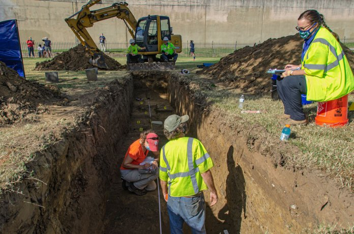 wide view down the trench of the Original 18 site with a backhoe in the background