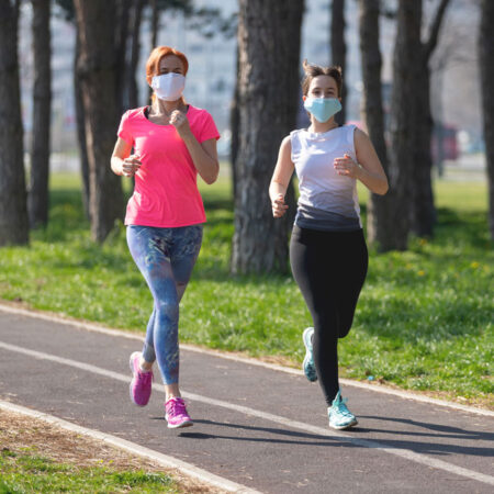 a photo of two women running on a track wearing face masks