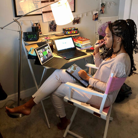 a photo of Nia Terry attending virtual class at her desk