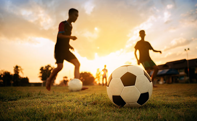 a photo of kids playing soccer at dusk