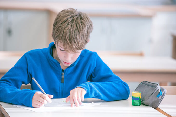 a student sitting at a desk and writing