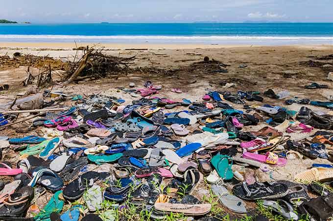 a photo of piles of flip flops at a beach