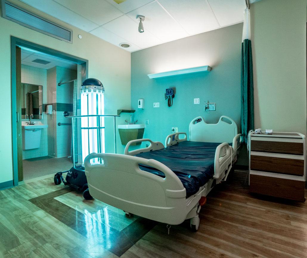 a photo of a hospital room and the Tru-D Smart UVC robot - a pillar of UV lights on wheels
