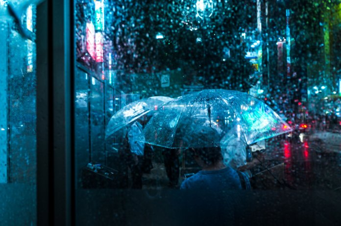 rain pours on people carrying umbrellas in Japan