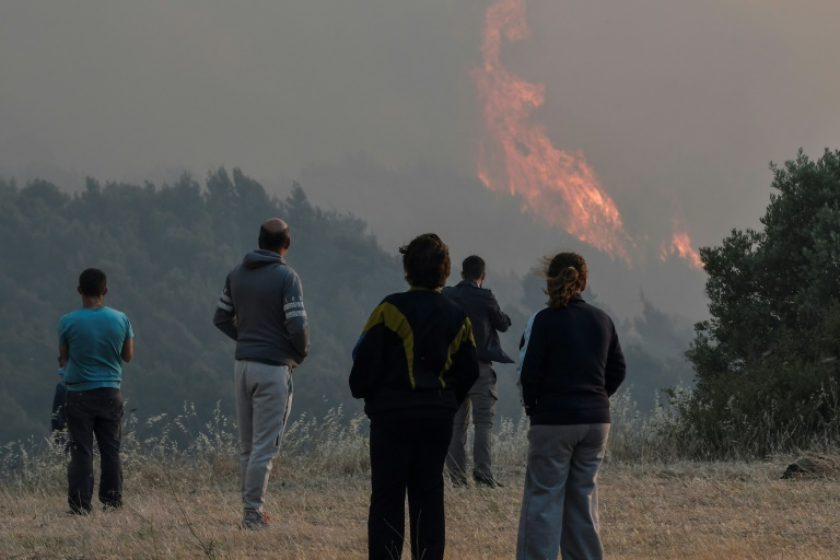Residents observe the flames of a forest fire near the village of Pefkaneas, west of Athens, on May 20, 2021 in Greece (AFP - LOUISA GOULIAMAKI)