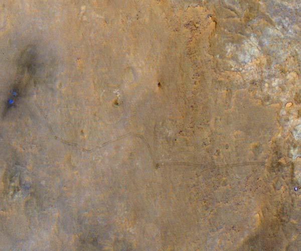 Links ziet u de plek waar Curiosity geland is. Het blauwe stipje rechtsonder is Curiosity zelf. Foto: NASA / JPL-Caltech / Univ. of Arizona.