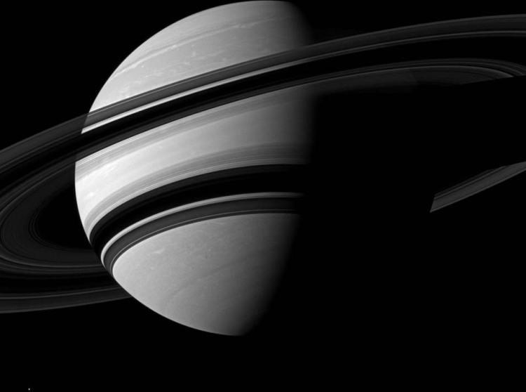 Op deze foto schittert Saturnus samen met zijn ringen. Wie goed kijkt, ziet helemaal onderaan (links) ook nog de maan Enceladus opduiken. Afbeelding: NASA / JPL-Caltech / Space Science Institute.