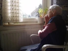 Elderly women sits next to a window.