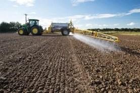 truck applying herbicide to crop
