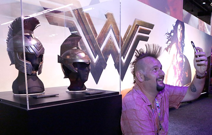 """Jim Wyatt takes a selfie next to the Queen's Guard Helmet and Amazon Army Helmet from the highly-anticipated film """"Wonder Woman"""" at the Warner Bros. Consumer Products booth at Licensing Expo 2016 on Tuesday, June 21, 2016 in Las Vegas. (Photo by Bizuayehu Tesfaye/Invision for Warner Bros. Consumer Products/AP Images)"""