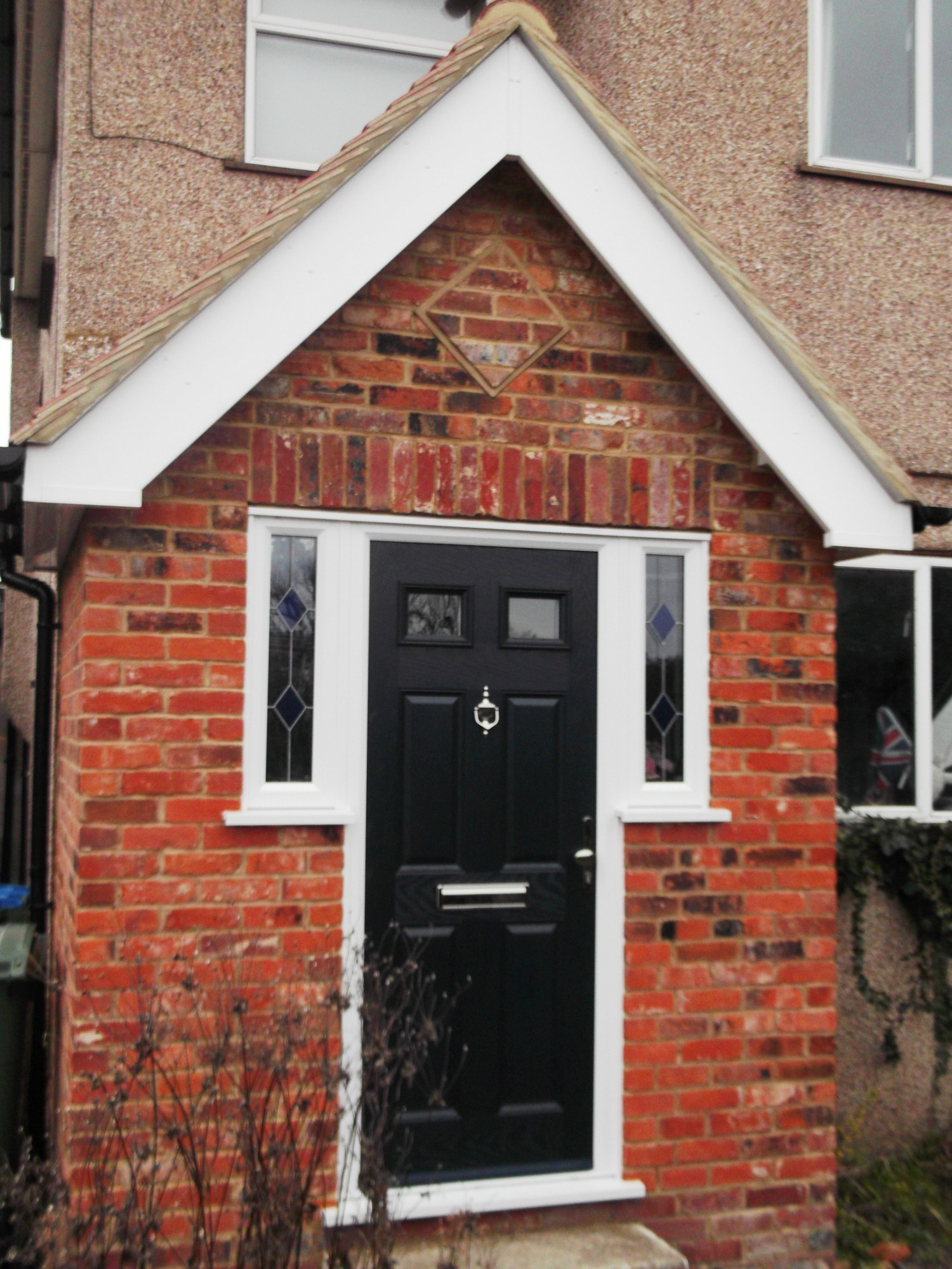 Porch front door with small decorative window panels