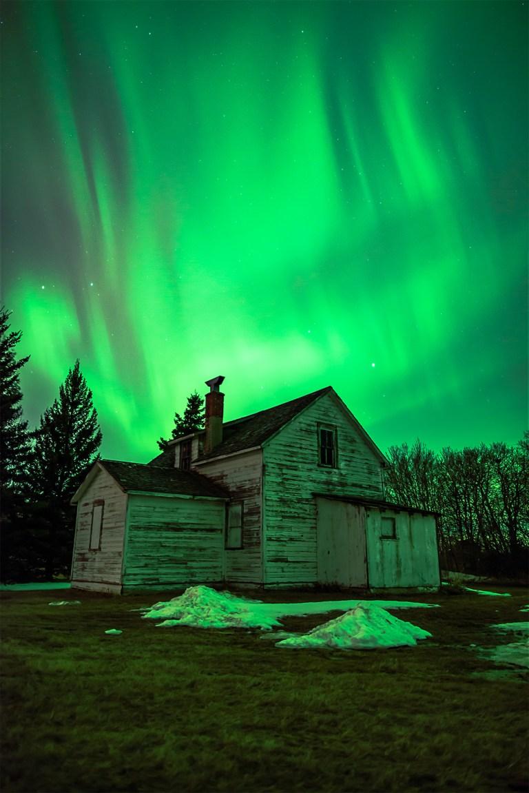 Aurora Borealis dances over an abandoned house in the Saskatchewan landscape