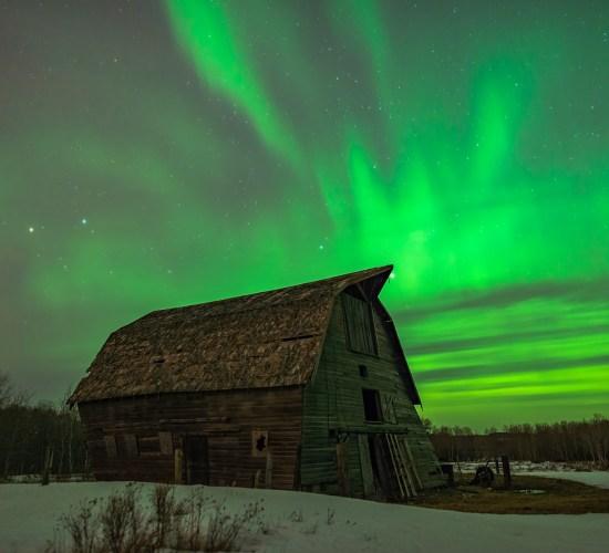 Aurora Borealis fires in the Saskatchewan night sky over an abandoned barn