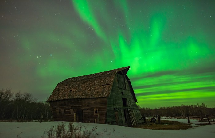 Aurora Borealis fires in the Saskatchewan night sky over an abandoned barn
