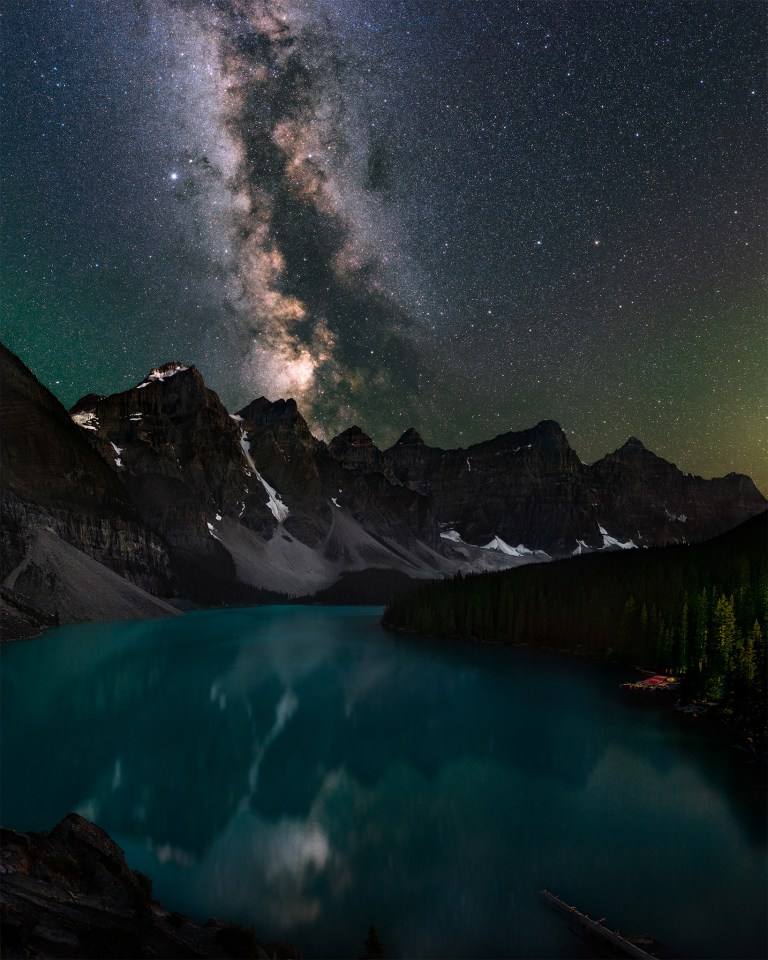 A night photograph of Moraine Lake, Alberta in Banff National Park. the milky way reflects in the pristine blue waters