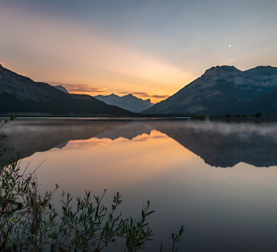 Sunset at lac Des arcs Alberta. A perfect reflection of the mountain range on a calm lake