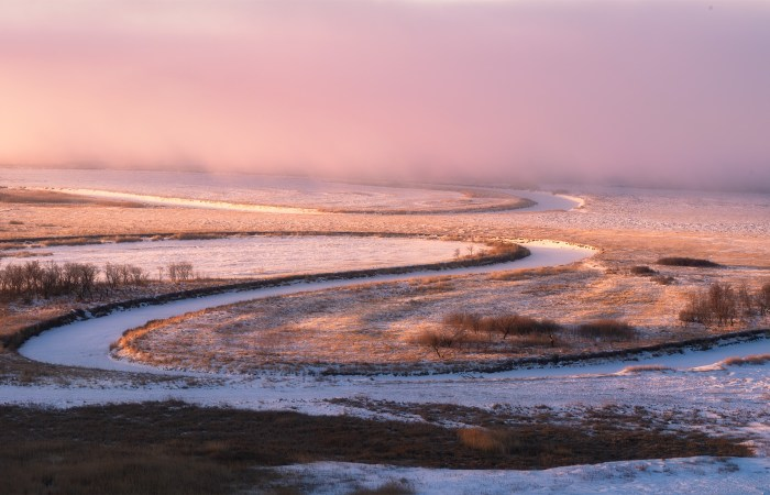 Light hits the Saskatchewan landscape as a frozen river winds through the scene