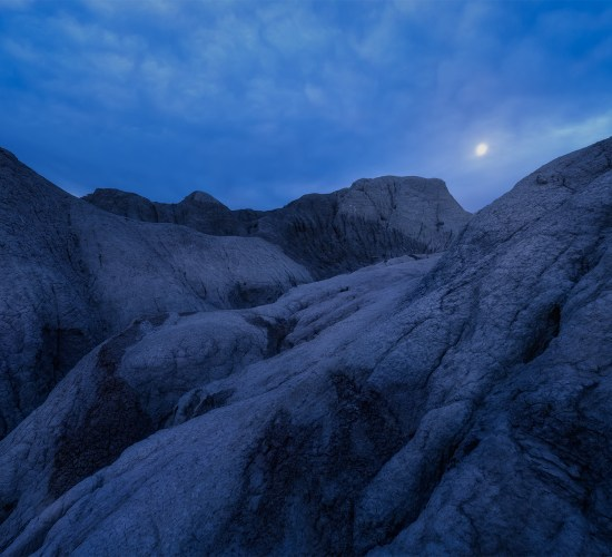 Night and Landscape Photography of a full moon over Saskatchewan badlands near Claybank.