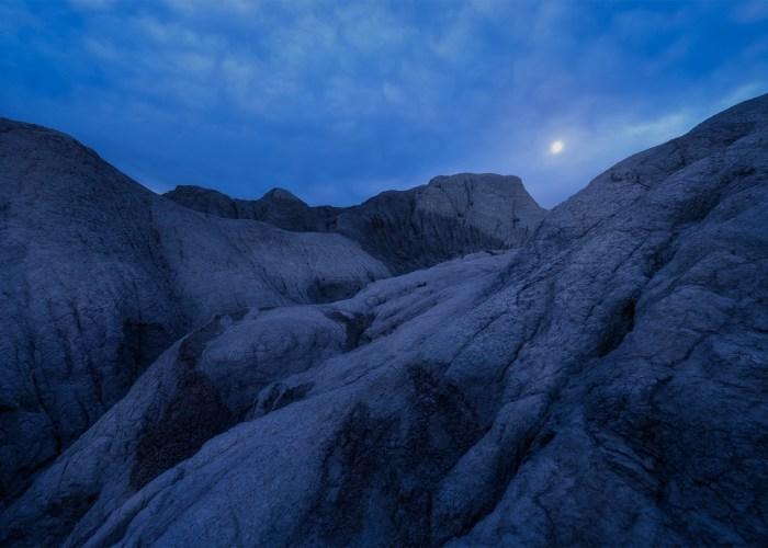 Night and Landscape Photography of a full moon over Saskatchewan badlands near Claybank.