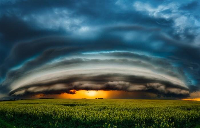 A landscape photograph of a supercell thunderstorm on the Saskatchewan prairie over a gold canola field