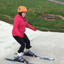 Young girl practicing balancing on skis during ASN snowsports session