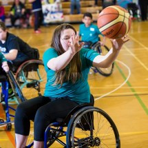 Female wheelchair basketball player throwing the ball with other players in the background