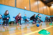 Young participants lined up in chairs and practicing boccia throws