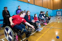 Two wheelchair users practicing boccia throws
