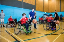 Two wheelchair basketball players practicing and supervised by Jen Scally from SDS