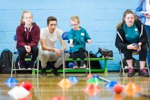 Two girls and a young boy practicing boccia throws supervised by coach